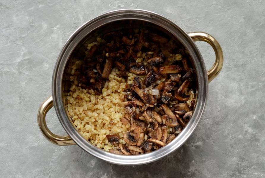 Переложите лук и грибы в кастрюлю к вареному булгуру. Перемешайте.
