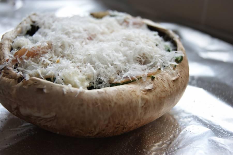 4. Шляпку гриба наполнить небольшим количеством начинки. Присыпать щепоткой панировочных сухарей, чтобы сделать более аппетитную корочку. Сыр натереть на мелкой терке и добавить сверху. Также грибы, запеченные в фольге в домашних условиях можно дополнить соусом - чесночным, например.