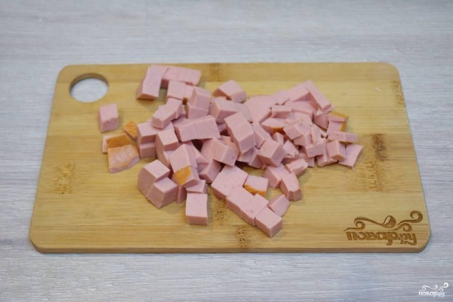Для приготовления классической окрошки нам необходимо взять колбасу. Вареную колбасу типа докторской следует нарезать небольшими кубиками. Для более полезного варианта окрошки можно взять отварную куриную грудку.