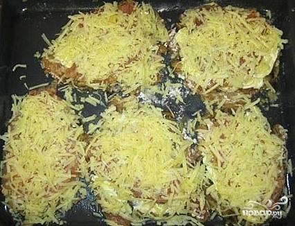 Смазываем отбивные сметаной и посыпаем сверху тертым сыром.  Запекаем в разогретой до 180С духовке примерно полчаса.