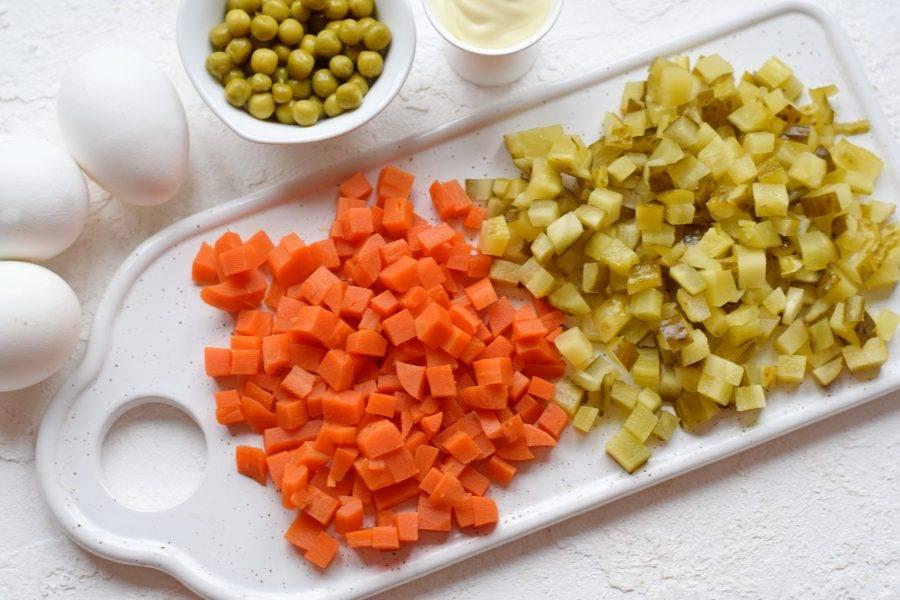 Вареную морковь нарежьте аналогично картофелю. Соленые огурцы нашинкуйте небольшими кубиками. Если при нарезке огурцов выделилось много сока, слейте его.