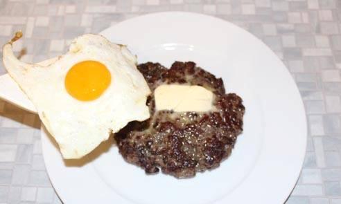 4. Перекладываем яйцо на бифштекс, но предварительно поверхность смазываем сливочным маслом.