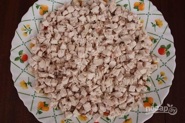 1. Первым делом вымойте и отварите филе. После остудите его немного, нарежьте мелкими кубиками и выложите на тарелку. Добавьте по вкусу соль и перец. Параллельно отварите яйца (вкрутую).