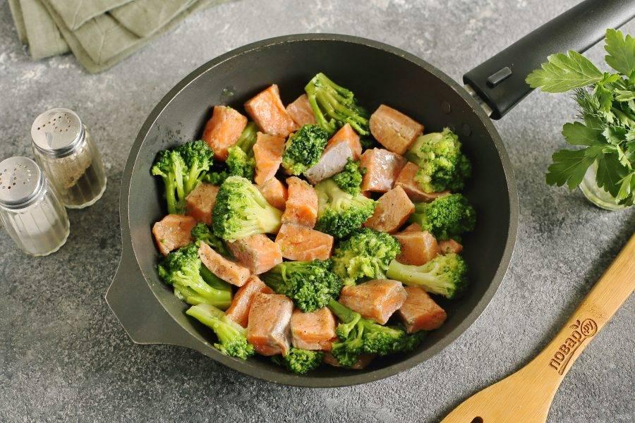 Разогрейте в сковороде масло. Выложите брокколи и рыбу.