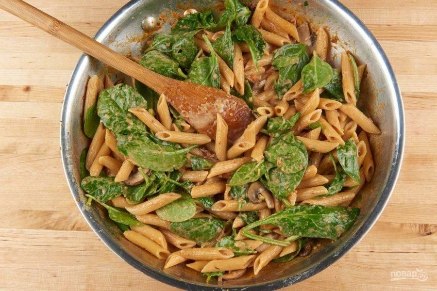 5. Далее добавьте шпинат, грибы с луком и натрите сыр (2/3 части). Готовьте блюдо ещё 1 минуту.