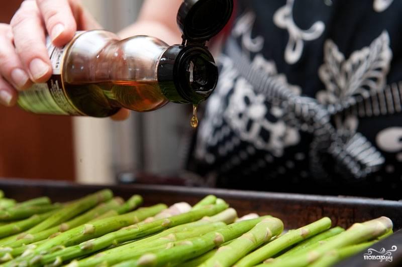 Распределите спаржу по всему противню одним слоем, затем полейте ее не много кунжутным маслом и соевым соусом.