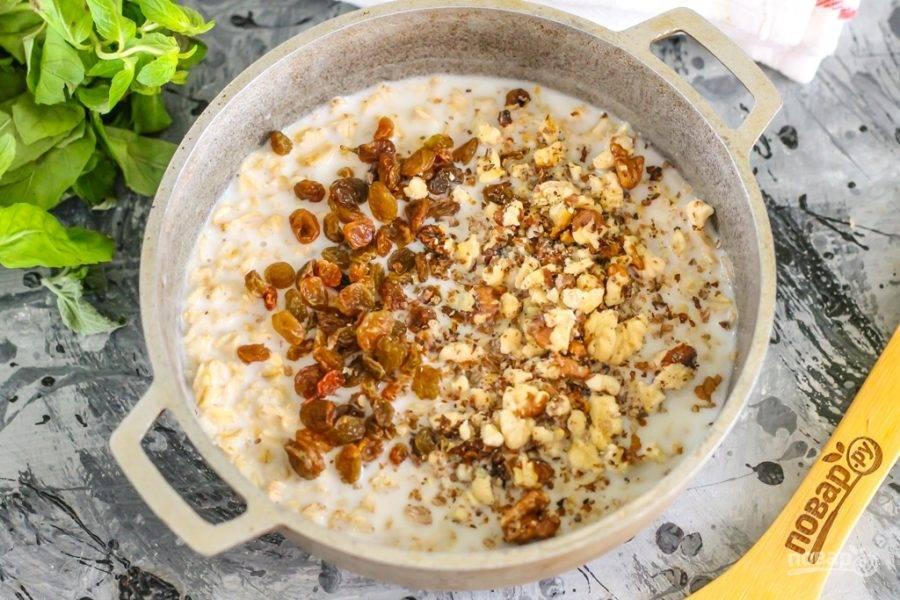Всыпьте в емкость изюм и ядра грецких орехов, слегка раскрошив последние в руках.