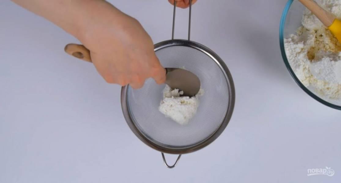 4. Горячий корж обрежьте по внутренней окружности сомкнутого бортика формы и полностью остудите на решетке. Творог протрите через дуршлаг, соедините с сахарной пудрой, ванилином и сметаной. Взбейте блендером в однородный крем.