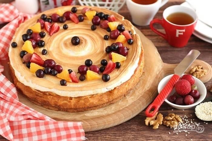 Украсьте пирог ягодами, шоколадом и орехами.