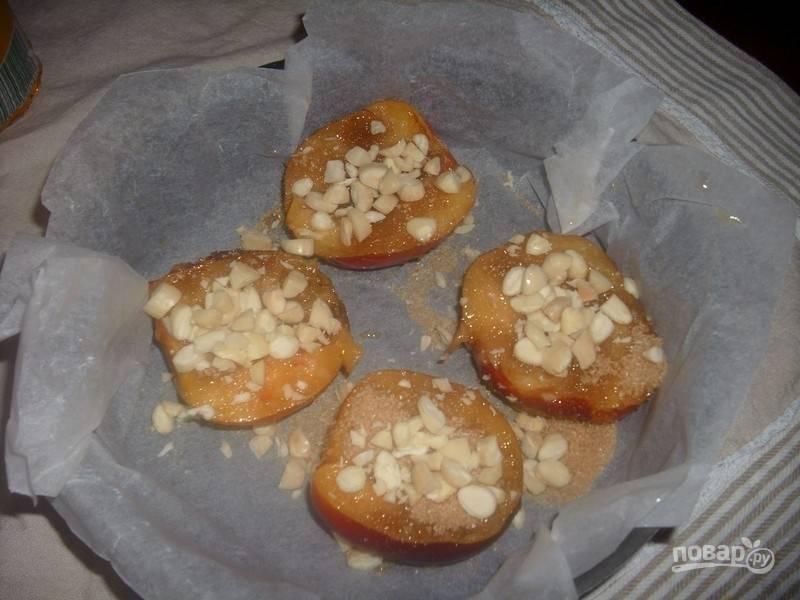 3.Щедро посыпьте персики сахаром и крупно нарезанными ядрами миндаля.