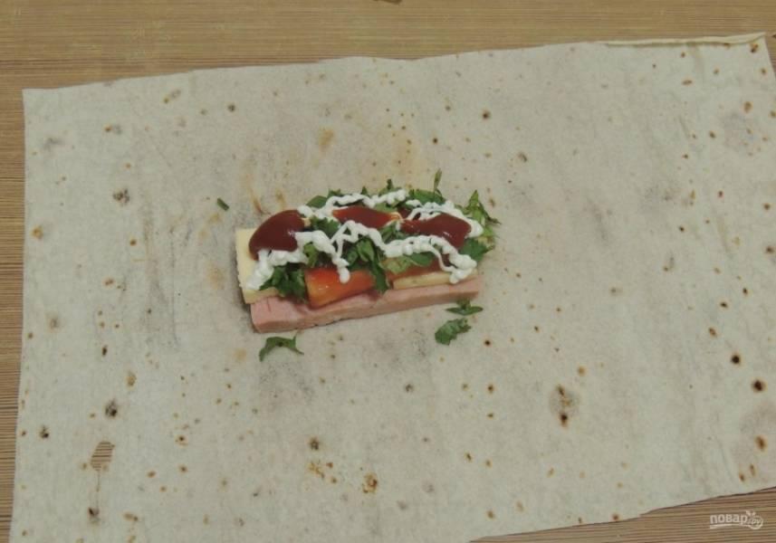 6.На лаваш выкладываю кусочек колбасы, затем сыр, помидор и зелень, поливаю все майонезом и кетчупом (майонез можно заменить сметаной).
