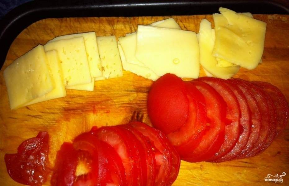 Далее снимаем с помидоров кожицу, нарезаем аккуратно колечками. Сыр режем ломтиками.