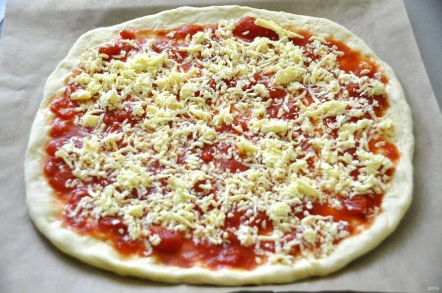 Раскатайте тесто в пласт и выложите на противень, застеленный пергаментом. Смажьте сверху томатным соусом, посыпьте натертой на терке моцареллой. Всю моцареллу сразу не выкладывайте, оставьте одну треть сыра для посыпки сверху.