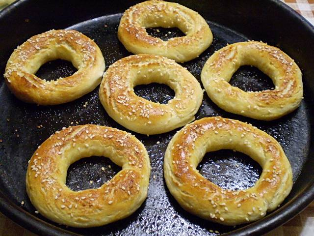 9. Выкладывайте бублики на смазанный маслом противень. Смазывайте желтком верх бубликов, посыпайте сахаром и кунжутом. Ставьте в разогретую духовку на 15 минут. Температура выпекания - 220 градусов.