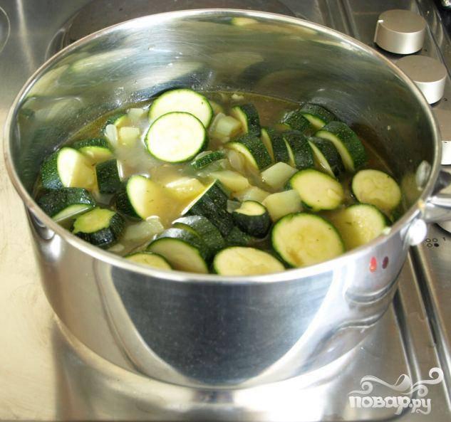 1.Помыть цукини, отрезать верхушки и низ, нарезать кружочками, толщиной около 1 см. Почистить картофель, нарезать его мелкими кубиками, примерно 1 см. Почистить и порезать лук. Почистить и мелко порезать чеснок. Мелко порезать зеленый лук и петрушку. Разогреть масло в кастрюле на слабом огне и добавить лук. Готовить 5 минут, постоянно помешивая. Добавить нарезанный кубиками картофель и готовить еще 15 минут. Часто помешивать, так как картофель может прилипнуть ко дну кастрюли. Добавить цукини и чеснок и готовить еще семь минут. Часто помешивать, чтобы ингредиенты не прилипли ко дну.