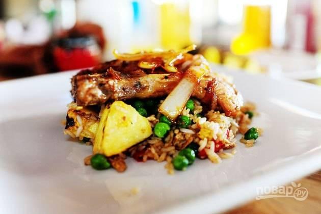 17. Все, можно подавать блюдо к столу. Сначала — рис с овощами и ананасом, затем — отбивная, сверху полейте все соусом, в котором жарилось мясо. Приятного аппетита!