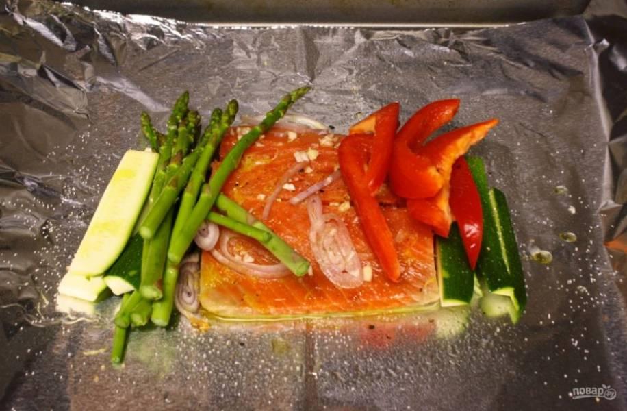 На 2 кусочка фольги выложите по куску филе, сбрызните соком, положите измельченный чеснок и вокруг уложите по половине овощей.