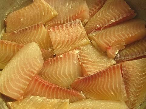Филе рыбы, если нужно, размораживаем, просушиваем бумажным полотенцем и делим на небольшие кусочки. Затем в форму для выпекания добротно наливаем масло и складываем туда кусочки рыбы (желательно в один слой).