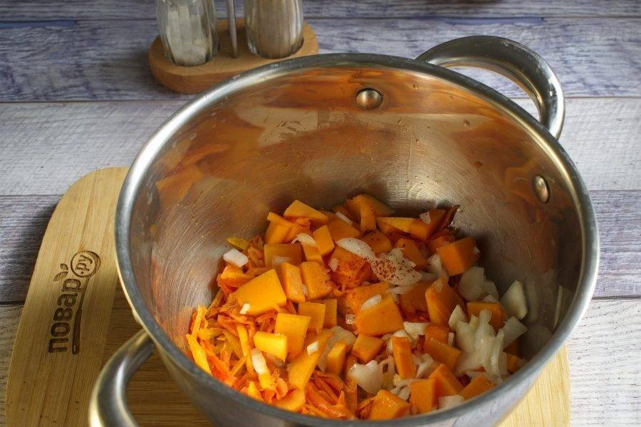 Морковь натрите на крупной терке, тыкву нарежьте мелкими кубиками, лук и чеснок измельчите. В кастрюле с толстым дном разогрейте растительное масло. Обжарьте морковь и тыкву до золотистого цвета в течение 3-5 минут.