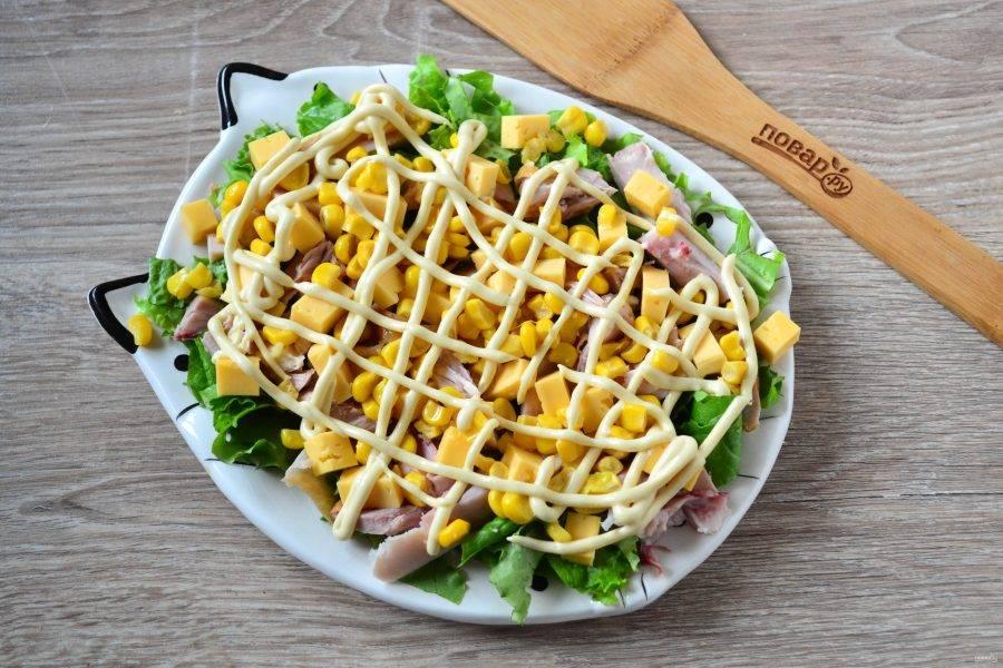 Покройте салат заправкой. Очень удобно переложить заправку в кондитерский мешок или пакет, обрезать край и покрыть салат красивой сеточкой.