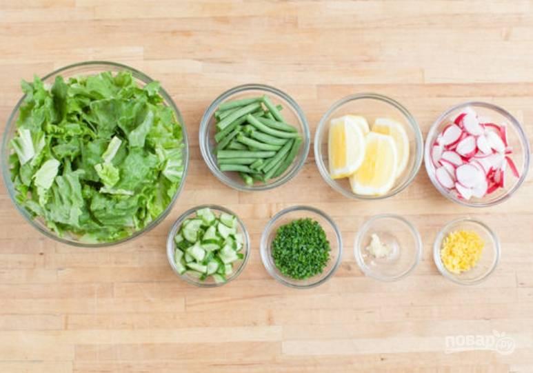 Салат порвите рукам на не очень мелкие кусочки. Зеленый лук измельчите. Порежьте дольками редис и огурец. Порежьте кусочками фасоль и лимон. Чеснок пропустите через пресс.
