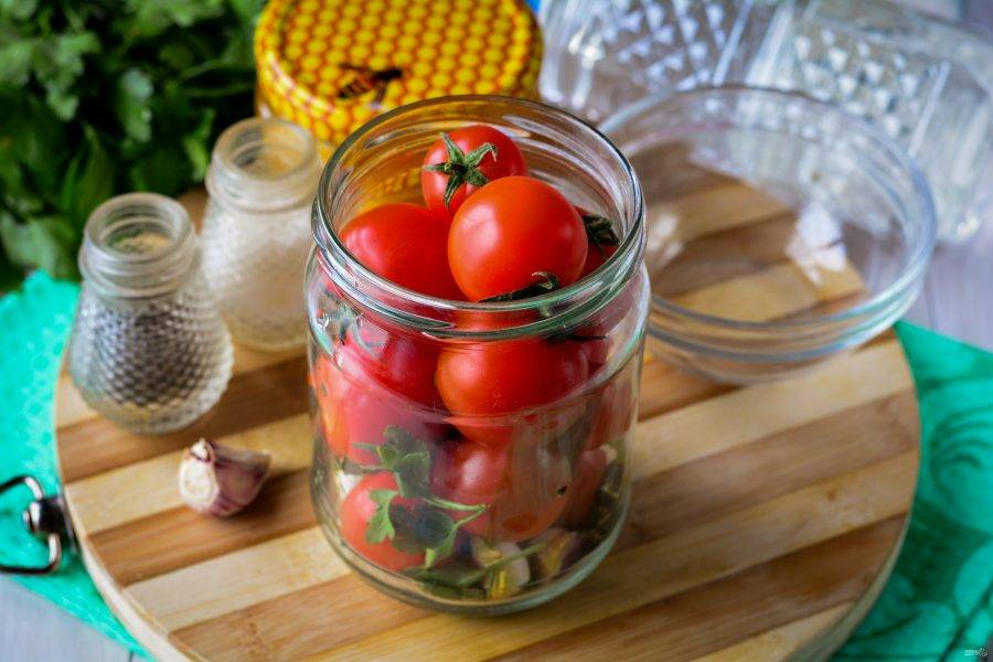Помидоры помойте и выложите в банки. Лучше используйте небольшие помидоры, они идеально укладываются и занимают немного места.