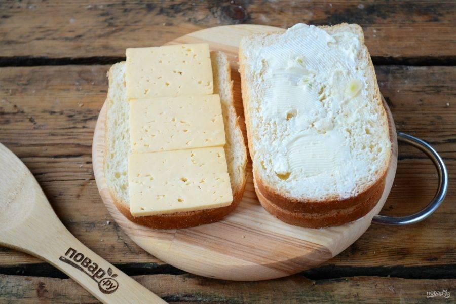 Примерно 2/3 сыра нарежьте тонкими ломтиками (можете использовать бутербродный сыр). Первый ломтик хлеба переверните маслом вниз и положите сыр. Сверху накройте вторым ломтиком хлеба, чтобы масло оказалось сверху.
