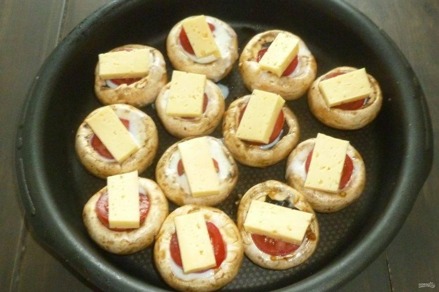 Сыр разрежьте на 12 ломтиков, помидоры черри - на половинки. Разложите половинки черри в шляпки, сверху выложите по кусочку сыра.