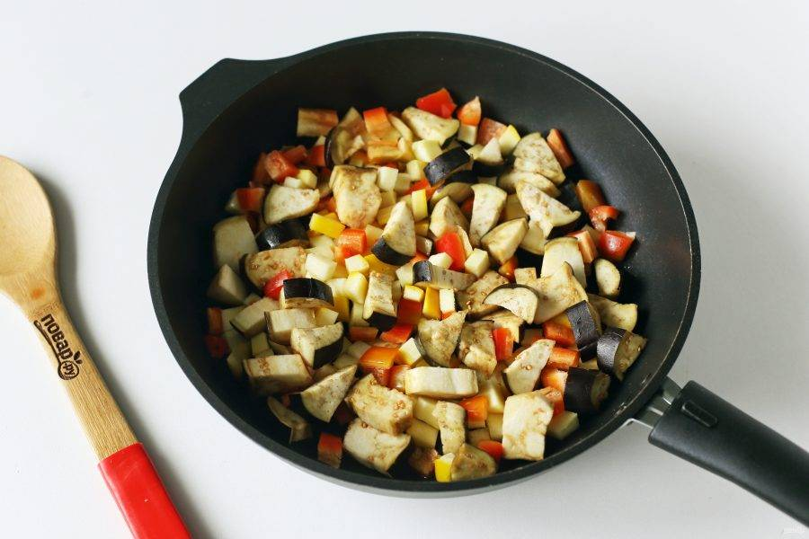 Все овощи, кроме помидоров, нарежьте крупными кубиками и переложите на раскаленную сковороду с маслом.