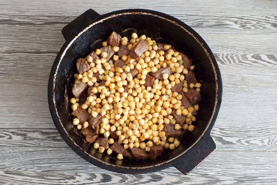 Когда жидкость в жаровне с мясом испарится, добавьте нут. Посолите, добавьте черный перец по вкусу.