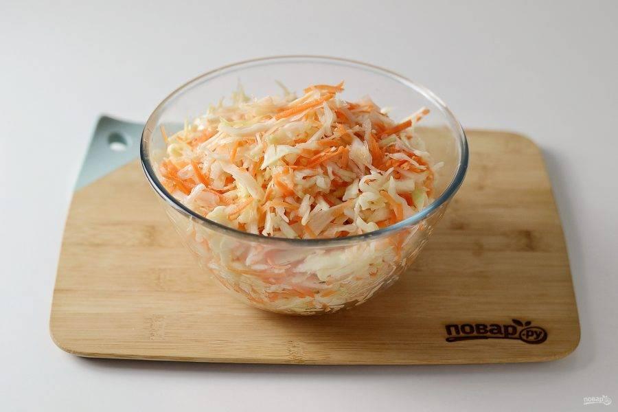 Капусту присыпьте солью и аккуратно руками пожмите ее, чтобы она стала мягче. Но не сжимайте сильно, чтобы капуста осталась хрустящей. Добавьте морковь, перемешайте.