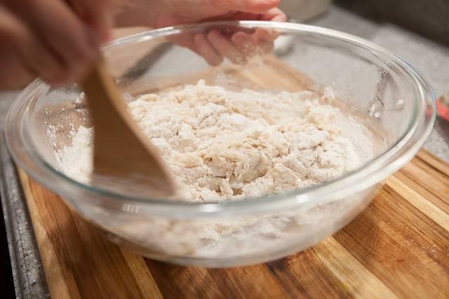 2. Затем добавить немного соли, разрыхлитель, масло и ввести постепенно, небольшими порциями, муку. Аккуратно перемешать.