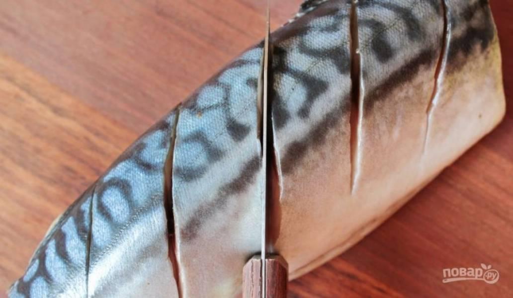 На боку рыбы сделайте несколько косых надрезов при помощи острого ножа. Затем переверните скумбрию и повторите все еще раз.