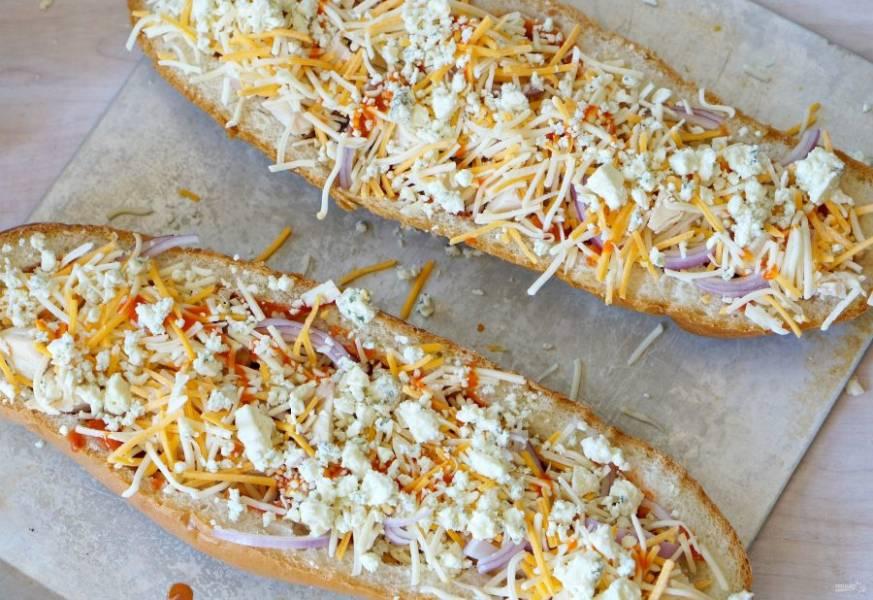 3.Вложите в багет курицу, затем добавьте луковицу. Натрите на мелкой терке чеддер и посыпьте им бутерброды, затем добавьте голубой сыр.