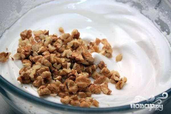 5.Очищаем грецкие орехи, нарезаем небольшими кусочками и добавляем их к взбитой массе. Все хорошо перемешиваем.