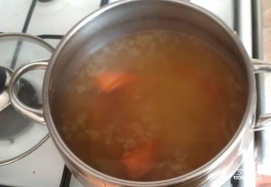 4. Нарезанные лук и морковь бросьте в кипящий бульон, который предварительно процедите через мелкое сито после того, как вынули из него мясо. Когда бульон вновь закипит, бросьте туда же предварительно нарезанный небольшими кубиками картофель и добавьте лавровый лист.