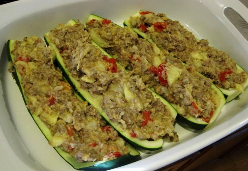 Смазываем форму для выпечки растительным маслом и выкладываем в нее кабачки, наполняем их плотно приготовленной начинкой.