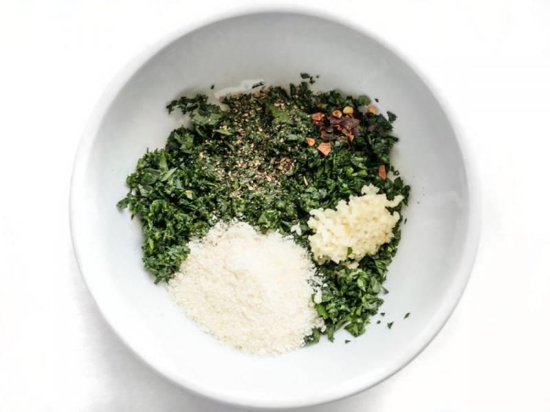 2.Помойте и измельчите петрушку, почистите и выдавите через чеснокодавку чеснок, натрите пармезан. В отдельной емкости смешайте петрушку, чеснок, пармезан, молотый перец, хлопья красного перца и соль по вкусу.
