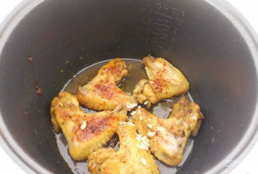 Через 30 минут крылышки переверните. Затем посыпьте их перцем чили и измельчённым чесноком. Оставьте уже без режима на 10 минут в мультиварке.