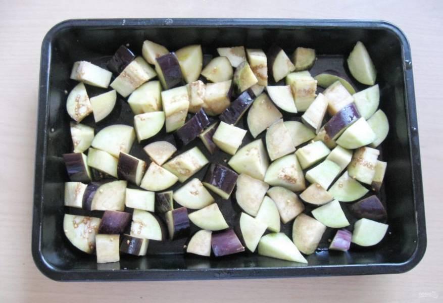 Нарезанные баклажаны выложите в миску, залейте рафинированным подсолнечным маслом и перемешайте. После этого распределите кусочки баклажанов ровным слоем на противне.
