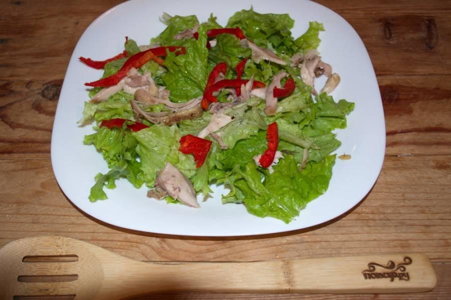 Болгарский перец нужно нарезать полукольцами. Выложите его в произвольном порядке на салатные листья.