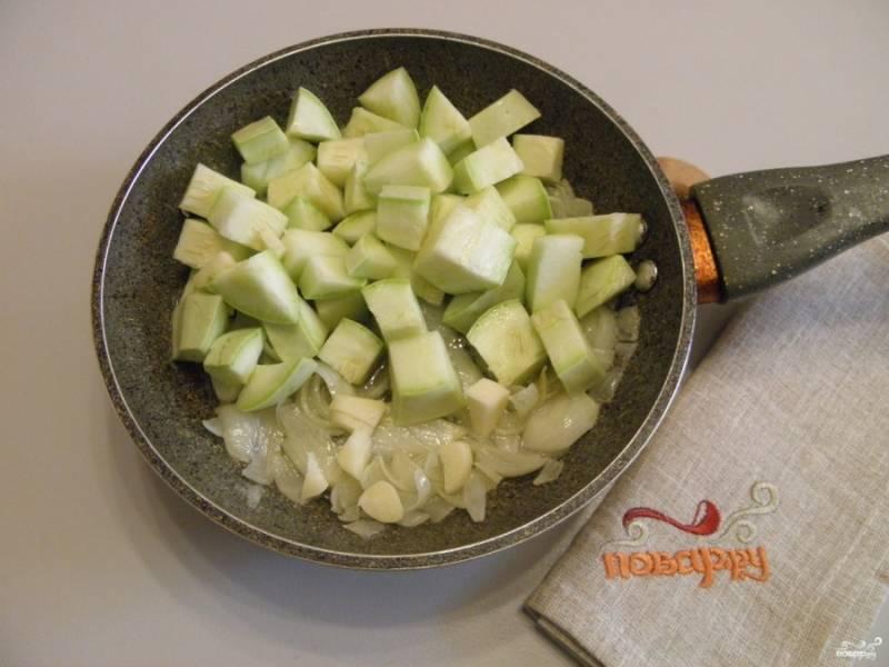 Кабачки порежьте кубиками крупно и добавьте к луку, туда же зубчик чеснока добавьте. Обжарьте пару минут все вместе.