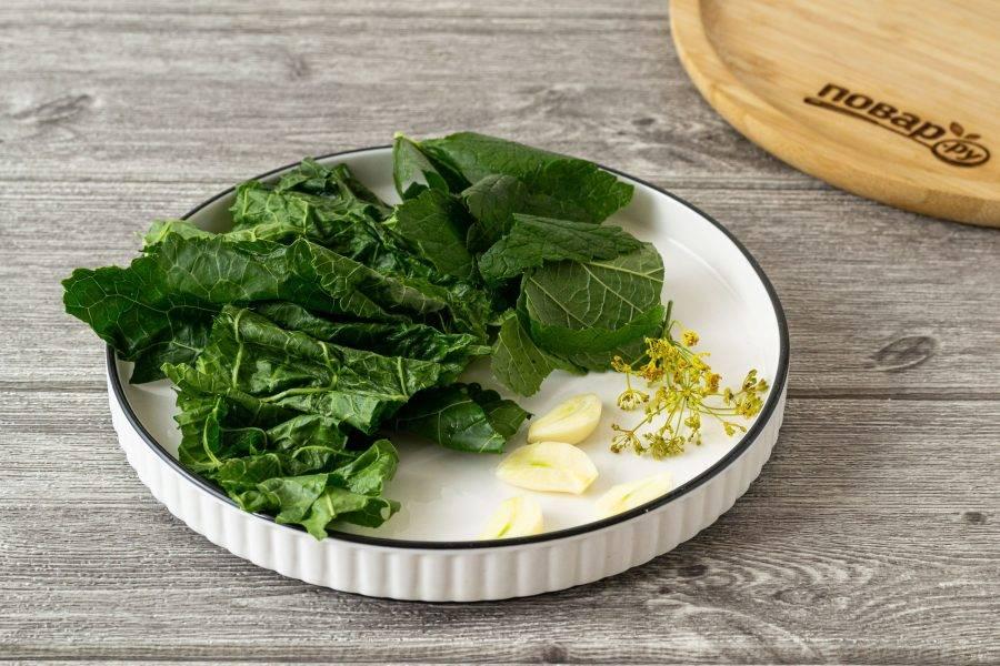 Помойте и обсушите засолочную зелень. Крупно порубите лист смородины и хрена. Чеснок очистите, разрежьте вдоль.