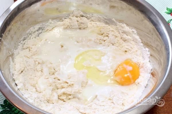 Добавьте яйцо, кефир, растопленное, но уже остуженное сливочное масло (40-50 г), приступайте к замесу. Вымешивайте тесто до мягкого состояния, при необходимости подсыпьте муку.