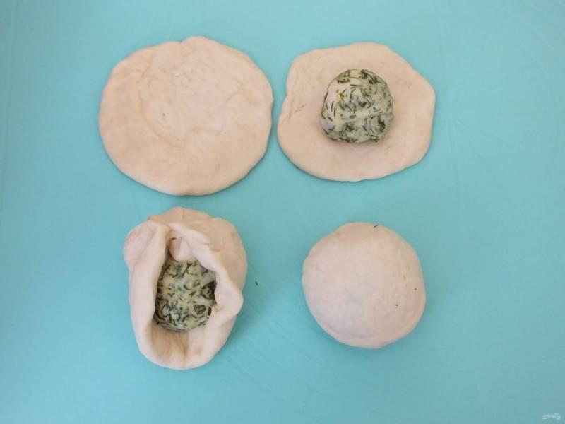 Формовка булочек. На ладони расплющите белое тесто в лепешку, на него выложите укропный шарик и защипните края к центру. Переверните и слегка прокатайте на рабочей поверхности.