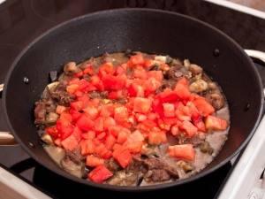 Наконец, добавляем помидоры, соль и перец по вкусу. Тушим до готовности, примерно 25 минут.