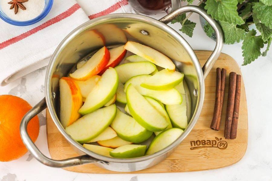 Яблоки промойте в воде, разрежьте на четыре части и удалите семенные блоки. Нарежьте каждую четвертинку ломтиками прямо в кастрюлю.