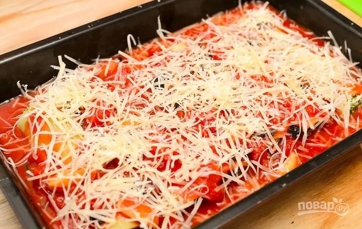 Духовку включите на 200 градусов. Каннелони выложите в форму. Вылейте на них томатный соус, присыпьте тертым сыром.