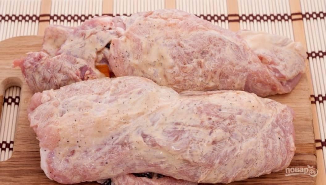 Выложите сухофрукты на мясо с соусом. Сверните свинину в рулеты.