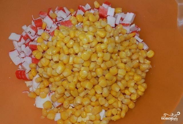 Затем добавляем в салат мелко нарезанные крабовые палочки и кукурузу.